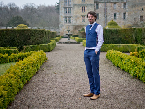 A full body landscape photo of Matt Dovey, dressed in a striped white shirt, blue tie and blue waistcoat, stood on a gravel path with low hedges in with a fountain some distance behind him and a stately home in the background