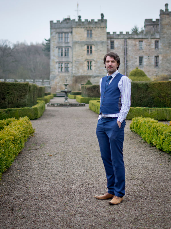 A full body portrait photo of Matt Dovey, dressed in a striped white shirt, blue tie and blue waistcoat, stood on a gravel path with low hedges in with a fountain some distance behind him and a stately home in the background