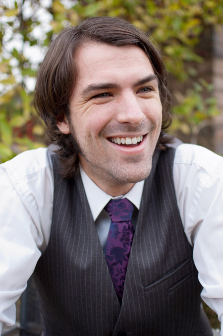 A photo of Matt Dovey, smiling, dressed in a white shirt, black waistcoat and purple tie, photographed against an out-of-focus background of leaves