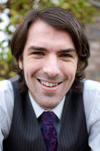 A headshot of Matt Dovey, dressed in a white shirt, purple tie and black waistcoat, looking at the camera and smiling