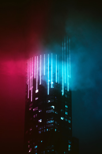 A skyscraper is lit through the fog with neon pink and blue lights