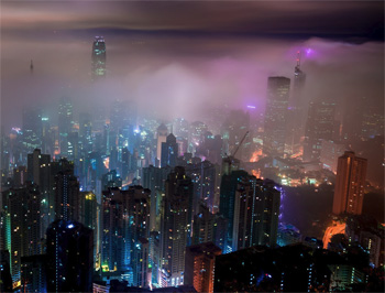 Skyscrapers lit in neon lights rise from the mist at night